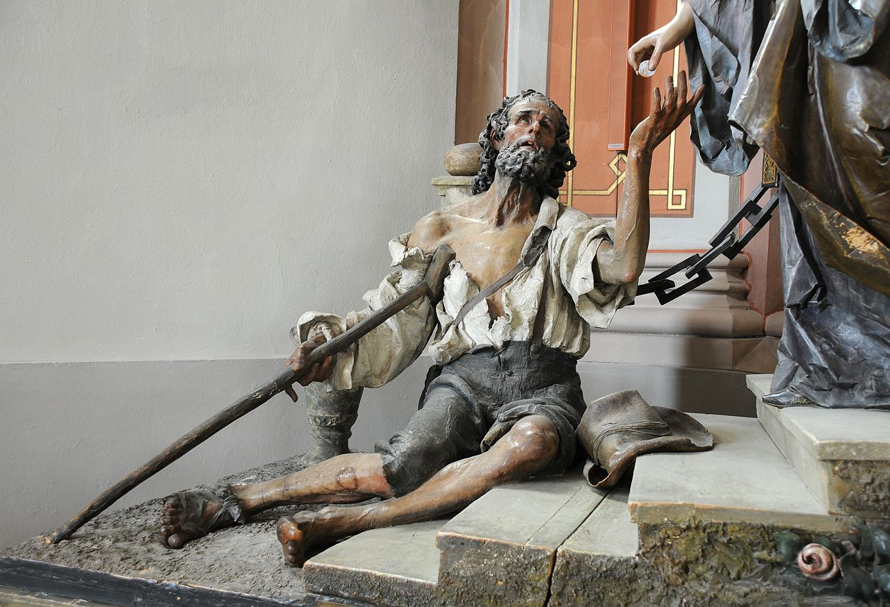 Der Bettler von Ludwig Moroder der Gruppe der Heiligen Elisabeth des Rudolf Moroder in der Pfarrkirche St. Ulrich in Gröden.  © User: Wolfgang Moroder, Beggar Saint Elisabeth Group, 2008. Quelle: Wikimedia Commons (CC BY-SA 3.0)