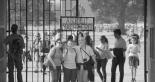 """Menschen posieren vor dem Schriftzug """"Arbeit macht frei"""""""