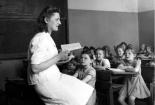 Lehrerin lesend vor einer Grundschulklasse