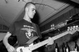 """Mitglied einer Naziband spielt Gitarre und trägt ein T-Shirt mit Reichsadler und Aufschrift """"Skinheads Deutschland"""", schwarzweiß"""