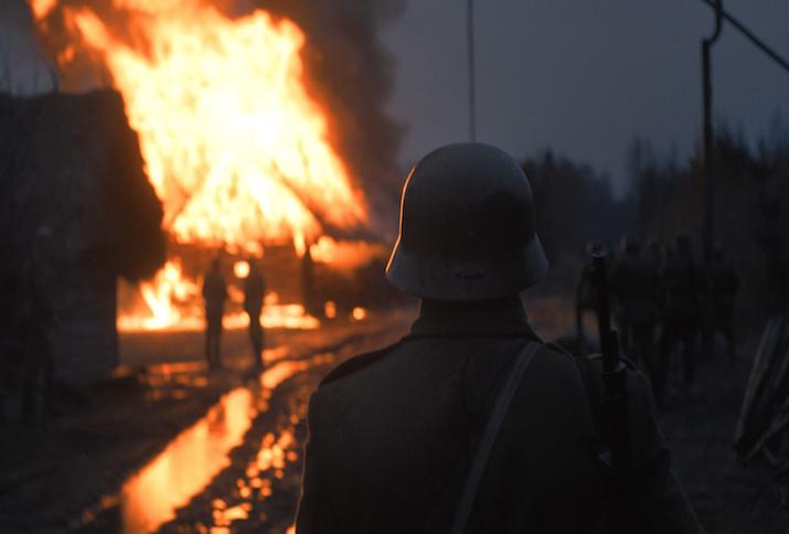 Eine Gruppe Soldaten und ein Soldat in Nahaufnahme von hinten in einer grauen Nacht stehen vor einem lichterloh brennenden Haus. Das Feuer reflektiert sich in den Pfützen