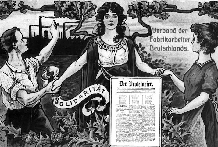 """Das Motiv entstand 1909 und zeigt Arbeiterin und Arbeiter sich in Solidarität die Hände reichend. Im Hintergrund rauchen die Fabrikschlote, im Vordergrund ist die Titelseite der Zeitung """"Der Proletarier"""" abgebildet"""