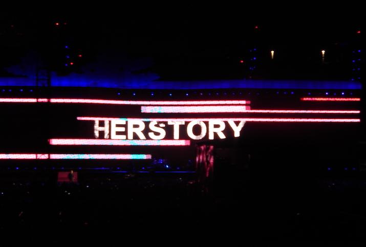 """Das Wort """"Herstory"""" in Leuchtbuchstaben auf einer verdunkelten Bühne."""