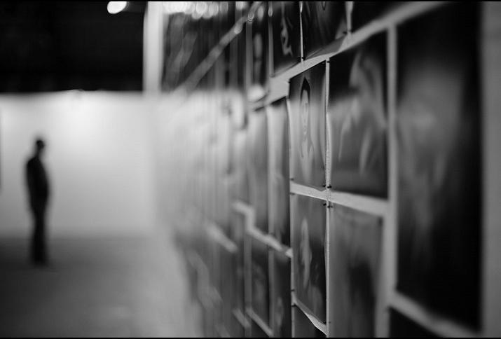 Schwarzweißfoto: Unscharfe Aufnahme eine(r) Ausstellungsbesucher*in vor einer Fotowand