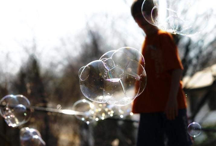 Seifenblasen im Sonnenlicht mit Kindersilhouette