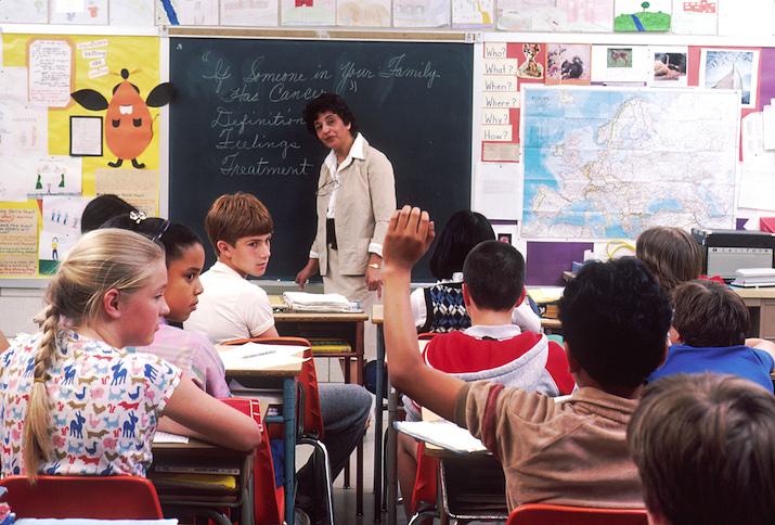 Lehrerin an der Tafel in vollem Klassenzimmer, 1985.