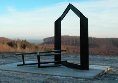"""© By Jimmy Fell (Archiv Jimmy Fell), """"Vertreibung"""" von Jimmy Fell im Skulpturenpark Deutsche Einheit. Ein vor das Haus geworfener Stuhl steht für die Vertreibung von Menschen aus ihrer Heimat, [Copyrighted free use], via Wikimedia Commons"""