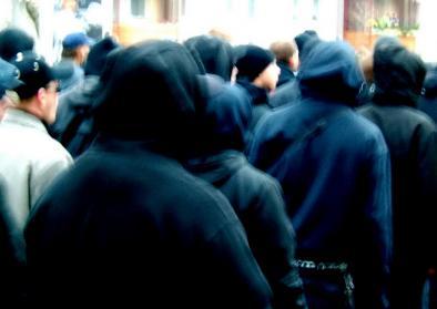 Rückansicht von Menschen mit schwarzen Kapuzen beim Nazi-Aufmarsch und Gegendemo