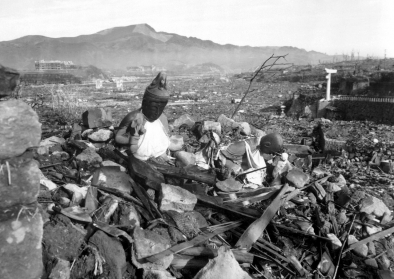 Battered religious figures stand watch on a hill above a tattered valley. Nagasaki, Japan. September 24,1945.
