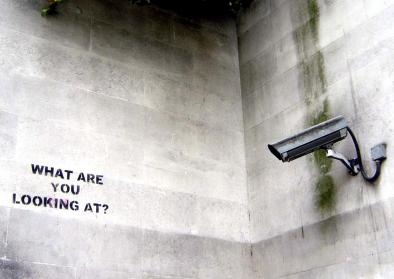 """Kamera ist auf eine leere Wand ausgerichtet, auf der """"What are you looking at?"""" steht"""