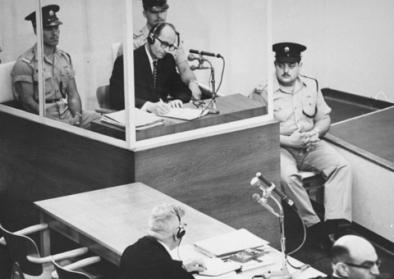 Adolf Eichmann takes notes during his trial