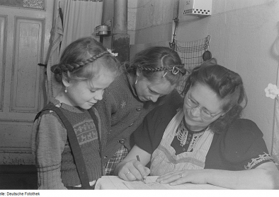 Portrait einer schreibenden Frau und zweier Mädchen