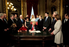 Trump am Schreibtisch umringt von Familie und Stab