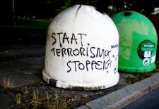 """Glaßmülltonne mit der Aufschrift """"Staat Terrorismus Stoppen"""""""