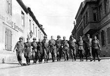 Amerikanische und sowjetische Soldaten laufen Arm in Arm in einer Reihe auf einer Straße im deutschen Torgau