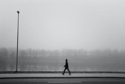 Schwarz-weiß Aufnahme eines Mannes im Profil, der eine Straße entlang läuft