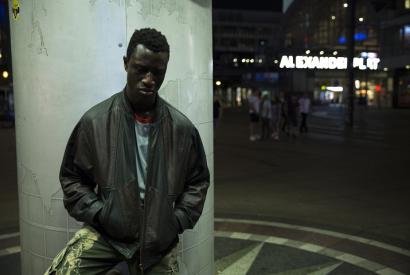 Hauptdarsteller lehnt an Säule und schaut zu Boden vor dem Berliner Alexanderplatz