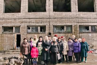 Menschengruppe vor einem maroden Gebäude, die einen Antrag an Putin stellen