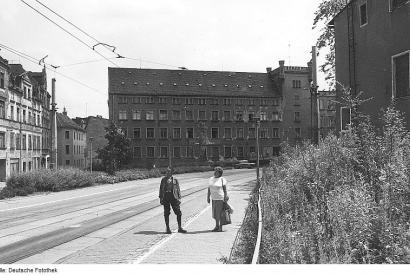 Schwarz-weiße Fotografie von einem älteren Ehepaar, das auf einer Straße vor einem verlassenen Gebäude steht