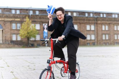 Museumsleiterin Sylvia Necker auf ihrem roten Klapprad auf dem Platz vor dem Museum