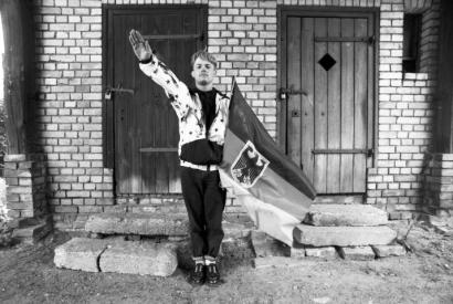 Schwarzweißfoto: Salutierender junger Mann mit Fahne