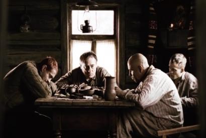 Filmstill; Vier Männer sitzen an einem Tisch in einer bäuerlichen Behausung
