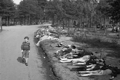 Young Boy Walks Past Corpses, dressed in shorts he walks along a dirt road lined with the corpses of hundreds of prisoners who died at the Bergen-Belsen extermination camp, near the towns of Bergen and Celle, Germany, April 20, 1945.