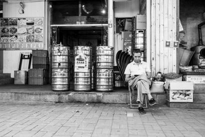 Schwarzweißfoto eines vor einem Biergeschäft sitzenden Mannes in Qingdao