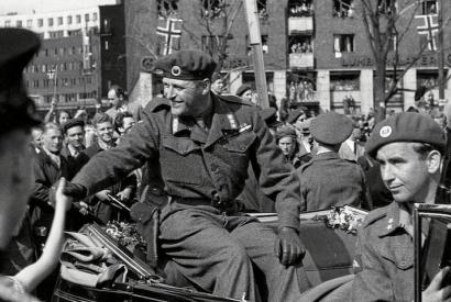 Kronprinz Olav bei seiner Rückkehr nach Norwegen, 13.05.1945; vor ihm sitzend (rechts im Bild) Max Manus