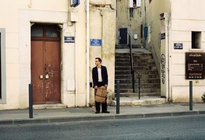 Filmstill aus Transit zeigt Franz Rogowski als Georg verloren vor einer beigen Wand stehend