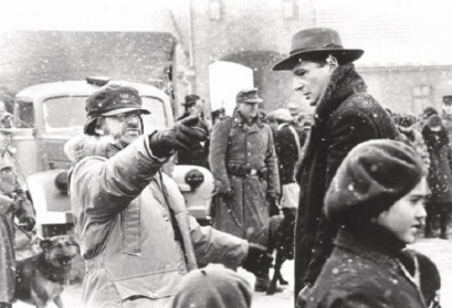 Film Still aus Schindlers Liste das Oskar Schindler in seiner Fabrik zu den jüdischen Arbeiter*innen sprechend zeigt