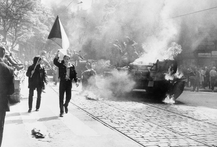 Einwohner von Prag mit tschechoslowakischer Flagge vor einem sowjetischen Panzer